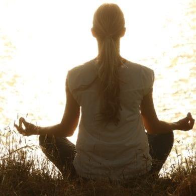 Fotografia della siluette di una donna intenta a praticare yoga, la disciplina che insegna il controllo del respiro o pranayama