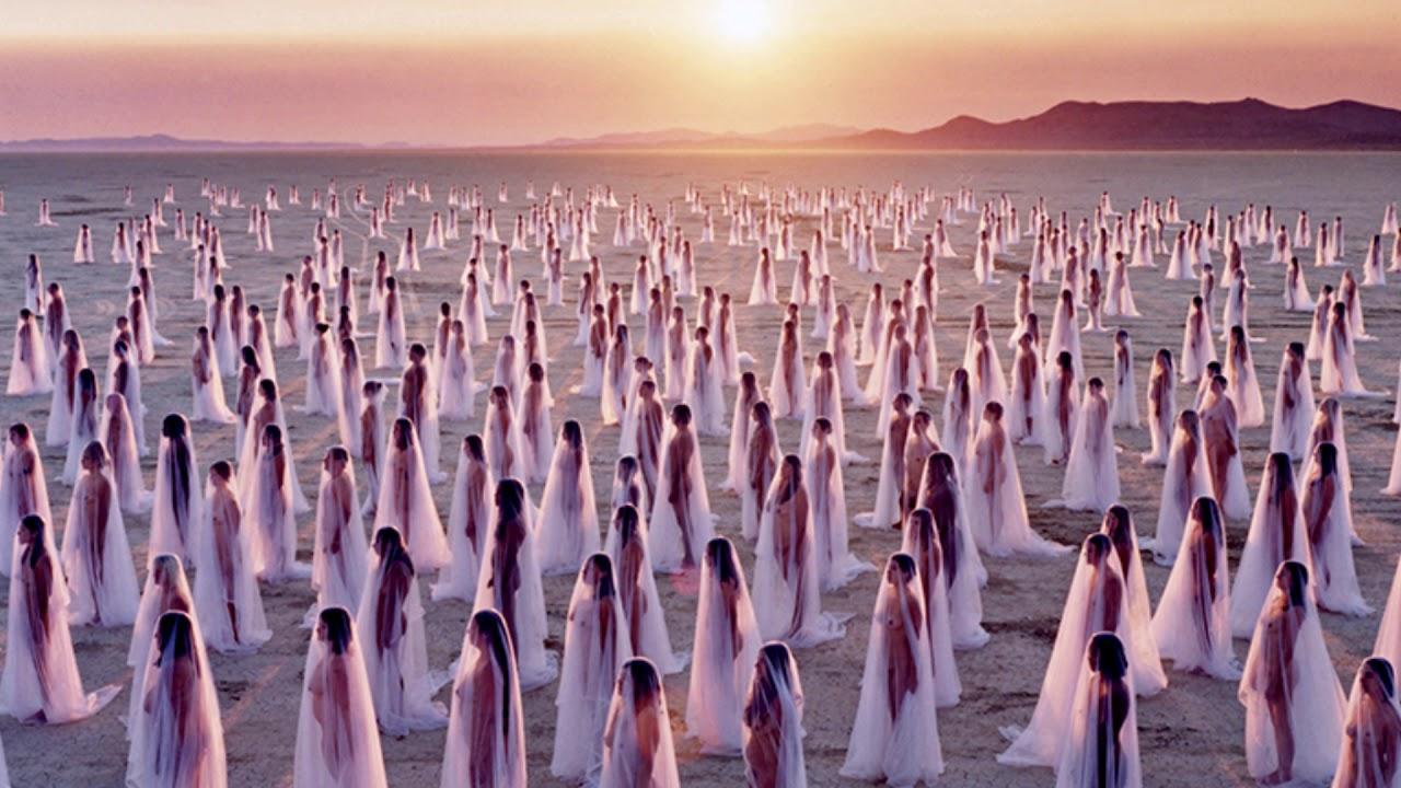 Persone nude in piedi coperte da un velo trasparente, nel deserto